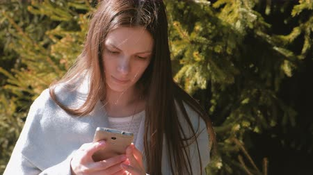 timeout : Portrait of beautiful brunette reading a message in her phone in park. Stock Footage
