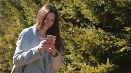 timeout : Portrait of happy beautiful brunette sending a message in her phone in spring park. Stock Footage