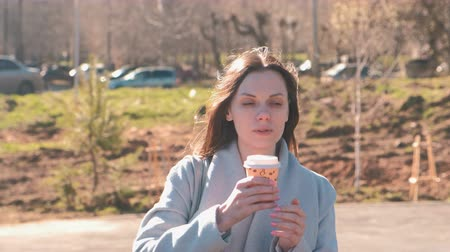 timeout : Portrait of young brunette woman in coat walks in city park and drinks coffee. Springtime. Stock Footage