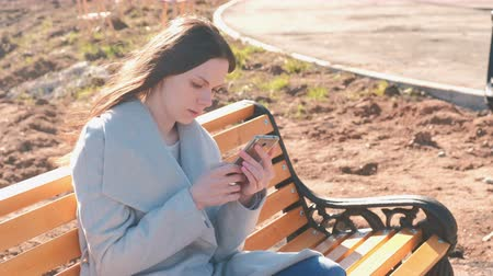 consulta : Portrait of beautiful brunette reading and typing a message in her phone sitting on the bench in park.