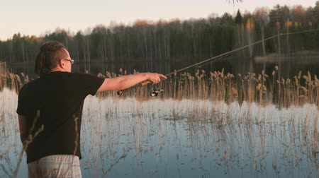 ужение : Fisherman on the pond. Young guy with dreads in glasses in a t-shirt fishing fish with rod.