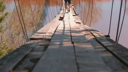 deep autumn : Close-up legs of family mom, dad and daughter walk on the old suspension bridge over the river.