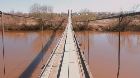 deep autumn : Man is walking on a suspended wooden bridge over the river. First person view. Stock Footage