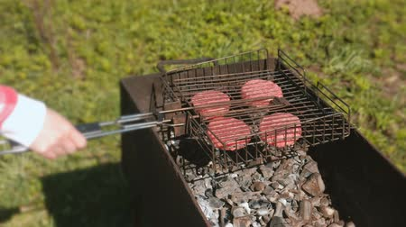 špejle : Woman puts a grill with chops on the brazier. Close-up hand.