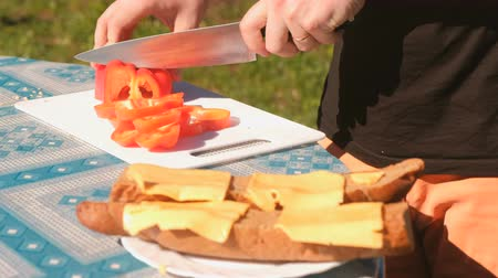 фарш : Young man cuts red pepper on the Board. Preparation of sandwiches. Close-up hands.