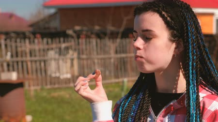 blue braid : Young woman eating meat sausage in the backyard in the spring on a Sunny day. Her son plays around. Stock Footage