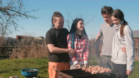 fogueira : Group of young people friends Barbecue shashlik meat on top of charcoal grill on backyard. Talking and smiling together.