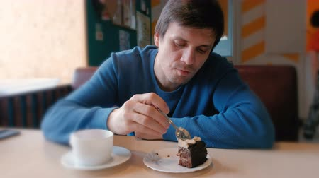 caloric : Young man eat a piece of cake in cafe. Stock Footage