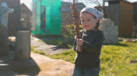 dacha : Little cute girl wants to eat barbecue shashlik on a skewer.