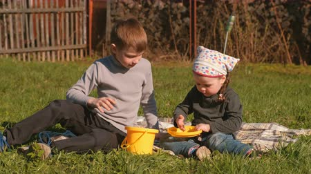 crawler : Brother and sister view earthworms sitting on the lawn in the backyard of the house. Stock Footage