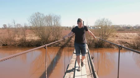 deep autumn : Young man is walking on a suspended wooden bridge over the river.