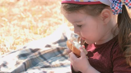 little finger : Little cute girl eats sandwich with bread and processed cheese. Family picnic. Licks her dirty fingers.