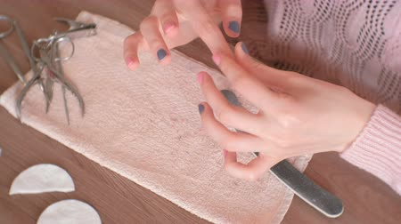 bojt : Woman puts the cream on the skin around the nails before removing the gel Polish. Hands close-up. Stock mozgókép