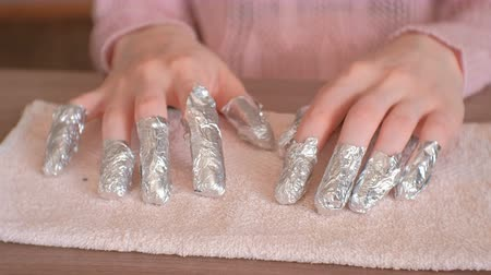 dosya : Removing gel Polish from nails. All fingers with foil on both hands. Close-up hand. Front view.