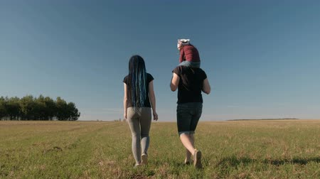 blue braid : Family day off. Mom, dad and daughter walk on the endless field. Beautiful summer landscape. Back view.