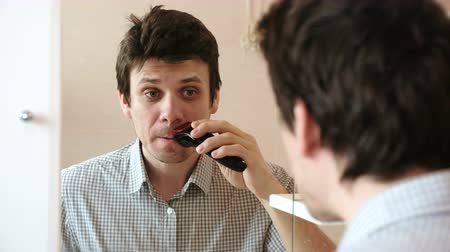 hangover : Machine shave facial hair. Young handsome man dry shaving with electric trimmer. Stock Footage