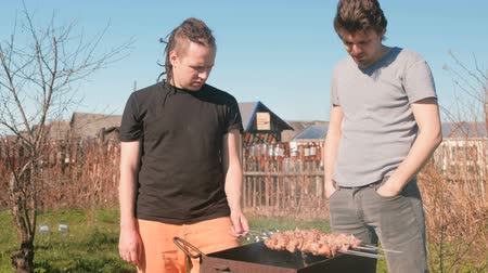 špejle : Two men friends cook shashlik meat on top of charcoal grill on backyard. Talking and smiling together.