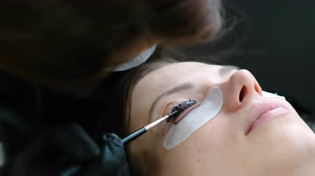 szempillák : Beauty treatment. Cosmetologist puts black paint on the lashes. laminating eyelashes. Closeup face side view.