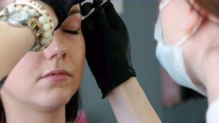 tweezing : Cosmetologist performs the procedure of correction eyebrow with tweezers. Closeup view.