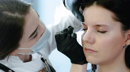 tweezing : Cosmetologist performs the procedure of correction eyebrow with tweezers. Front closeup view