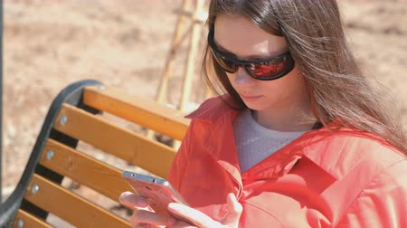 manikür : Young brunette girl in sunglasses watches a video on the phone sitting in the Park on the bench.