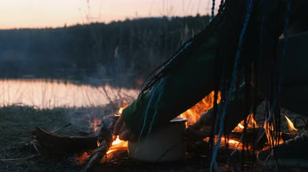 романтический : Burning bonfire of dry branches in the forest in riverbank close-up.