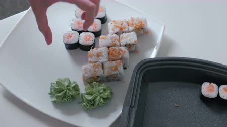 cheese packaging : Woman puts rolls and wasabi from plastic packaging in a plate. Close-up hands.
