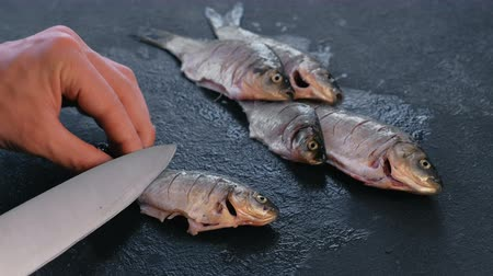 tail fin : Man makes cuts on carp fish on black table. Cooking fish. Close-up hand.