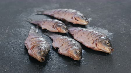 специальный : Carp in spices on a black table close-up. Side view.