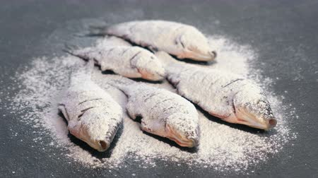 окропляет : Carp fish in spices and flour on a black table.