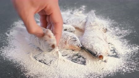 tail fin : Man dips carp fish in flour on a black kitchen table.