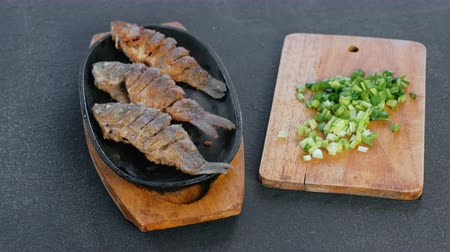 serving board : Fried fish carps on a tray on a black table and green onions on the Board. Serving dishes.
