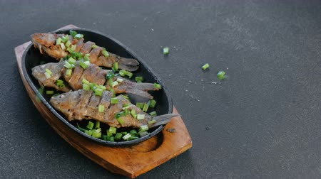 serving board : Fried fish carps on a tray sprinkle with green onions. Stock Footage