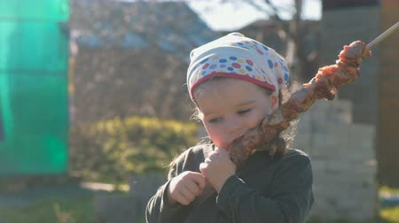 dacha : Little cute girl eats barbecue shashlik on a skewer. Stock Footage