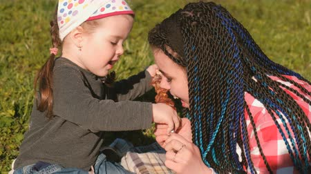 blue braid : Mom feed her cute little daughter with meat shashlik barbecue on a skewer in the backyard. Stock Footage