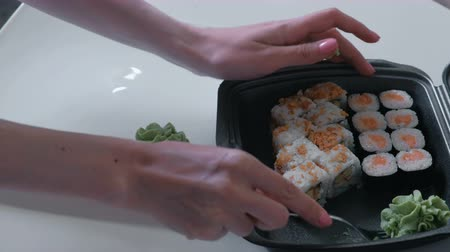 cheese packaging : Woman puts rolls and wasabi from plastic packaging in a plate. Stock Footage