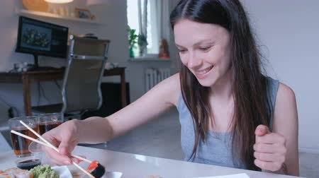 cheese packaging : Young woman brunette eats rolls with wood sticks at home. Stock Footage