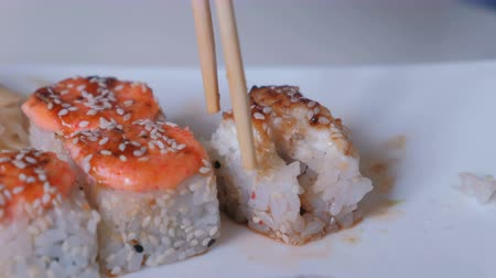 kaviár : Roll falls apart when a woman takes it with chopsticks. Hand close-up.