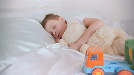 ziewanie : Seven-year-old boy sleeping with his toys bear and plastic car. Wideo
