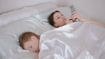 cobertor : Mom woke up and browsing internet in her mobile phone. Her son is still asleep.