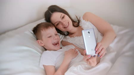 arrasto : Mom and son take selfie on her mobile phone. Vídeos