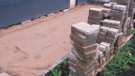 csempe : Laying paving slabs in front of the building. Sand and paving slabs in rows. Close-up view.