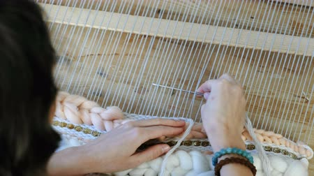 смелый : Weaving on a loom. Closeup womans hands running on a loom. Threading the needle through the strands of frame and fasten the yarn with scallop.
