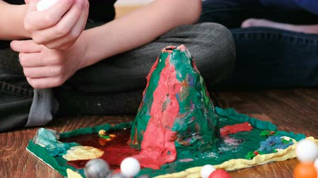 construtor : Mom and son make experience with plasticine volcano erupts foam at home. Chemical reaction with gas emission. Stock Footage