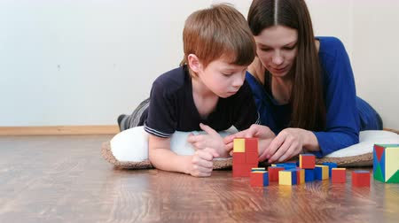 logic : Mom and son playing together wooden colored education toy blocks lying on the floor. They build a red box.