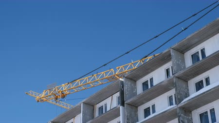 vég : Construction of a multi-storey building. Cranes turns to the side over the roof in sky background. Stock mozgókép