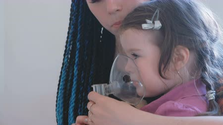 inhalacja : Little cute girl inhaling through inhaler mask with her mom. Use nebulizer and inhaler for the treatment.