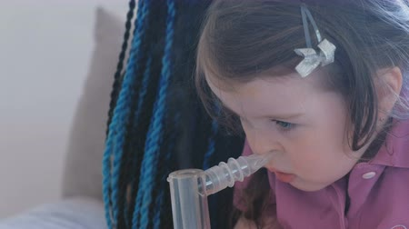 sedative : Little cute girl inhaling through inhaler mask with her mom. Use nebulizer and inhaler for the treatment.