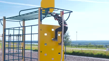 upstream : Boy climbs on a climbing wall holding the rope on the Playground.