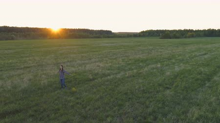 açıklık : Woman walking on the field at sunset, arms out to the sides with flowers in her hand. Stok Video